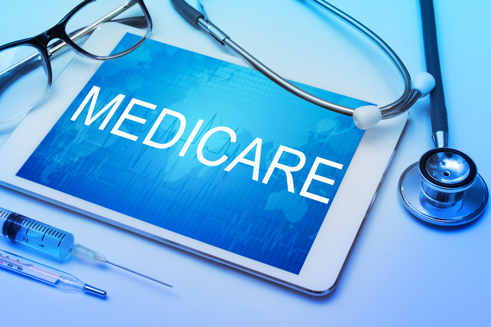 Medicare,Word,On,Tablet,Screen,With,Medical,Equipment,On,Background